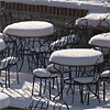 Unattended white tables in beer garden Lavka under Charles Bridge